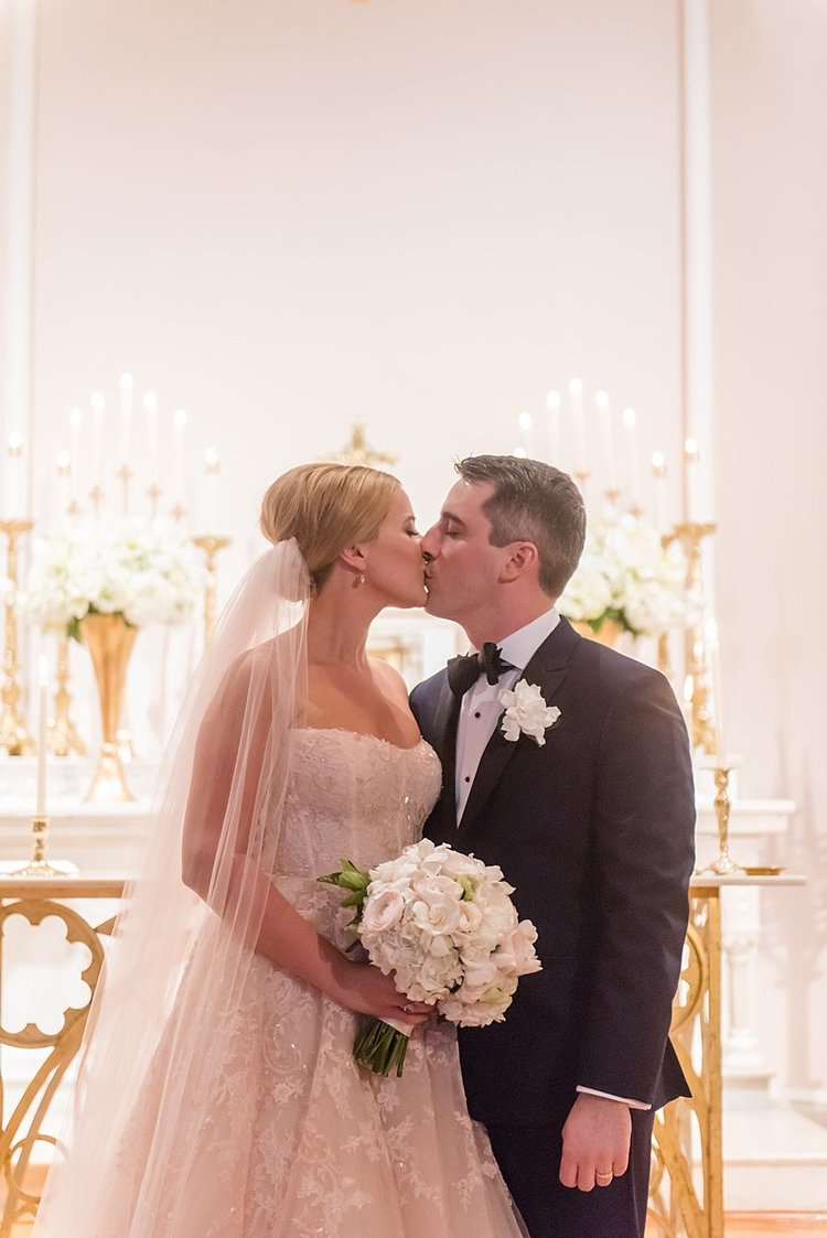 couple kissing after being announced bride and groom with lush white flowers on the alter