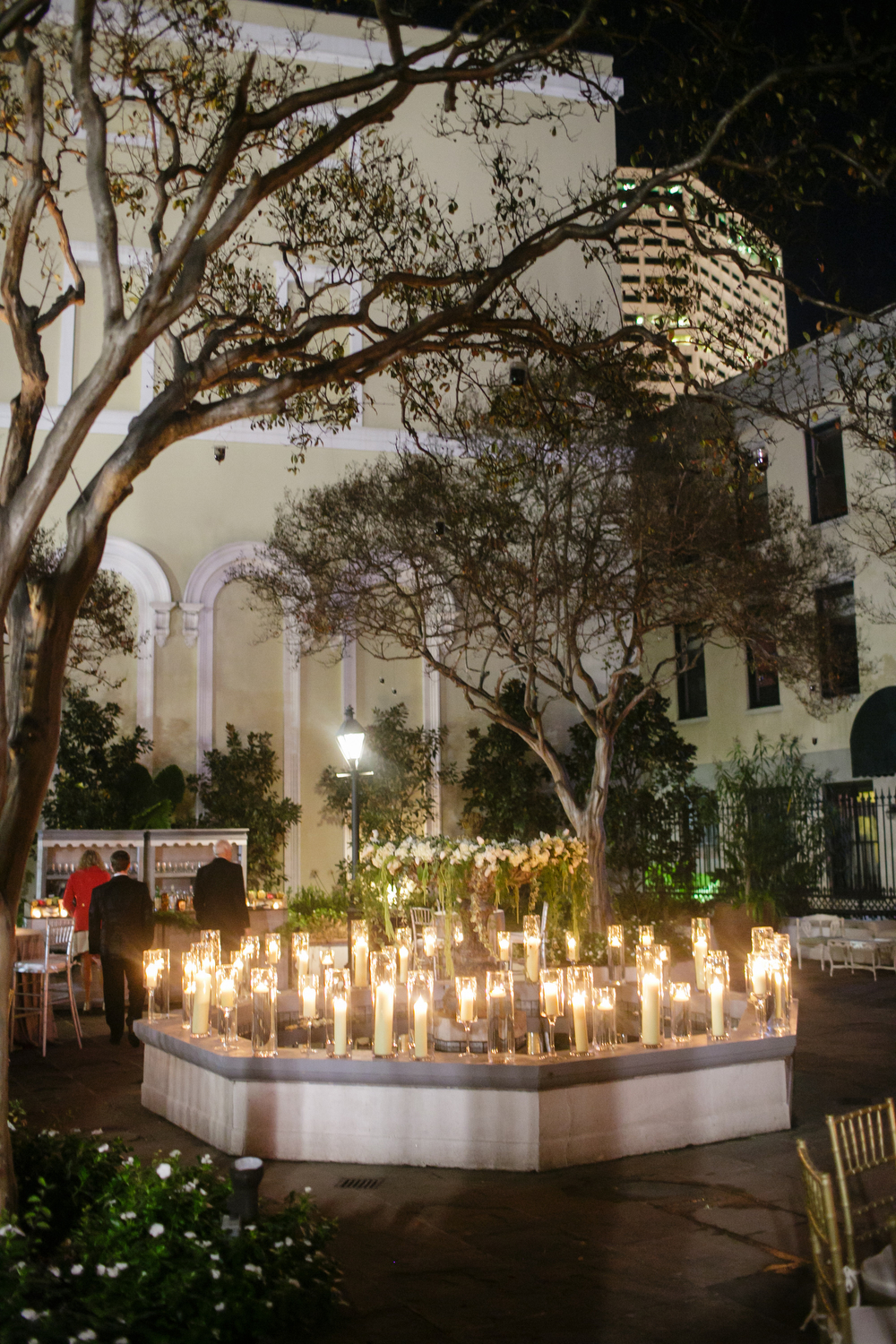 lots of pillar candles in glass hurricane vases surrounding the edge of a fountain in a courtyard at night