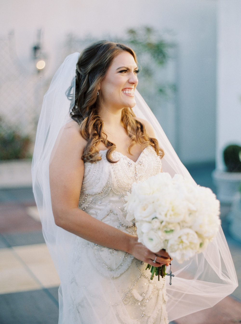 excited bride smiling and holding a white floral bouquet in her wedding dress and veil