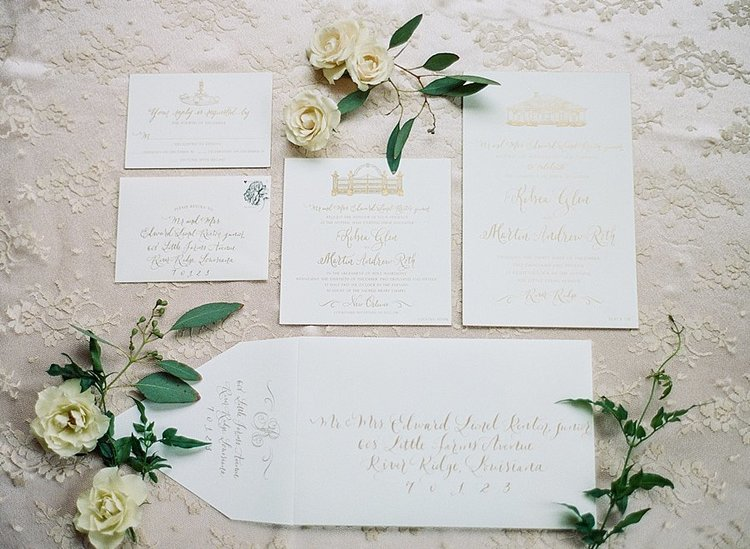 delicate white flowers placed around a simple yet elegant wedding invitation