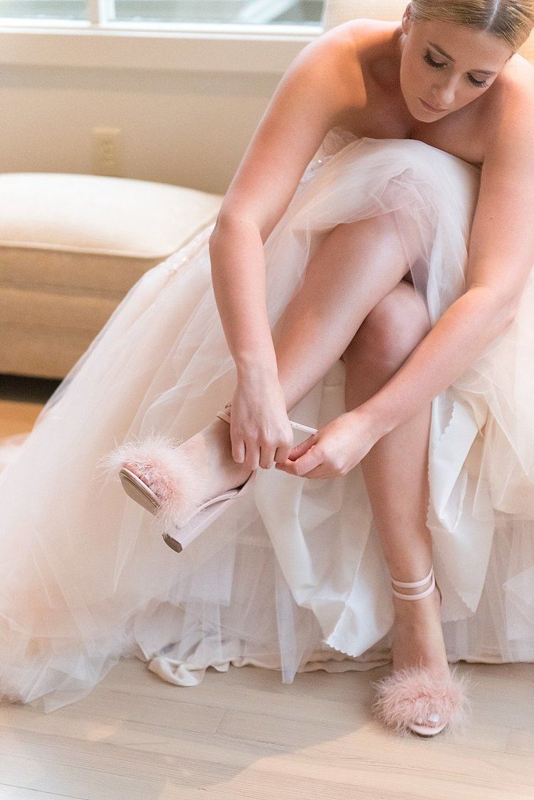 A bride putting on her blush pink shoes with her wedding dress tule laying over her