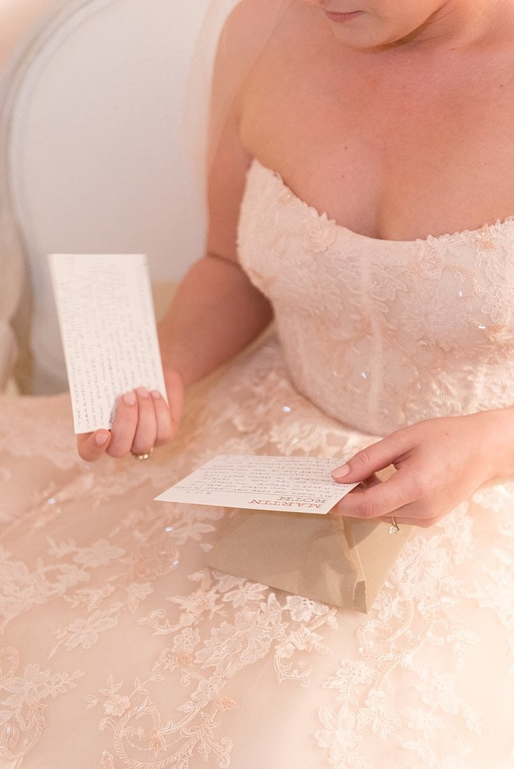 Bride sitting in her strapless sequin wedding dress reading hand written letters