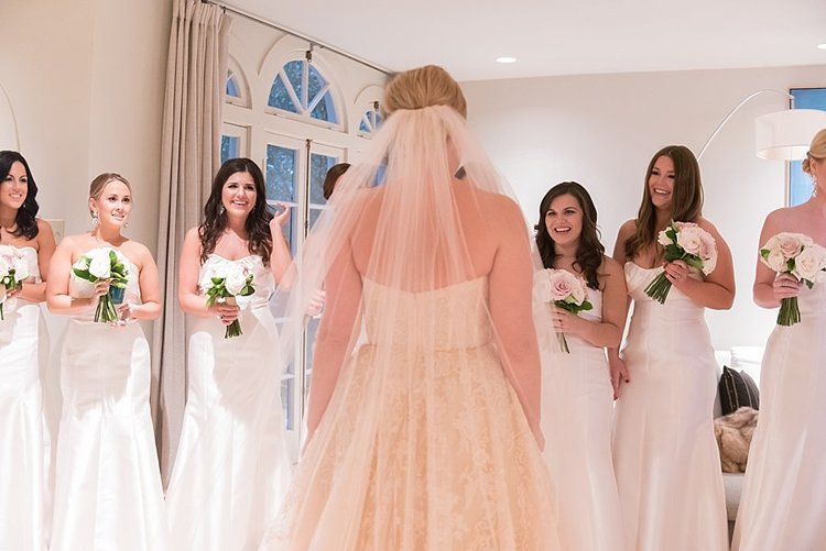 a bride facing her bridesmaids with a long white veil and bridesmaids in white dresses with white and green flowers