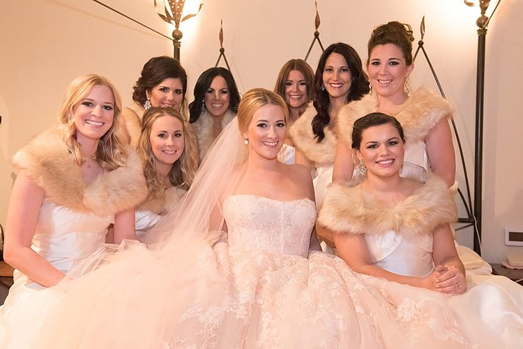 bride in wedding dress, bridesmaids in white dresses and fur raps around shoulders