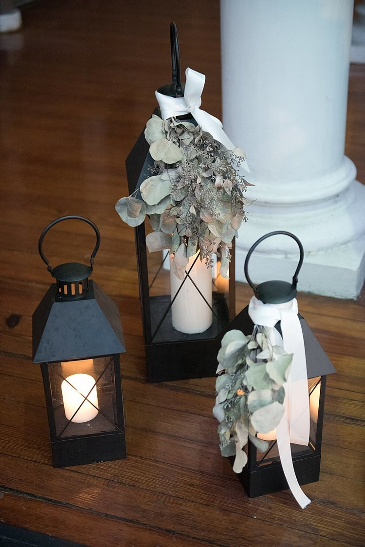black lanterns, candles and green eucalyptus hanging over