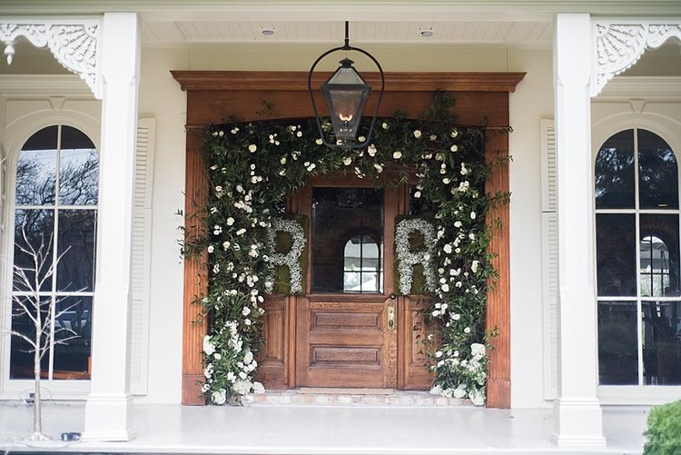 greenery draping over wooden door with white columns and initials made out of white flowers