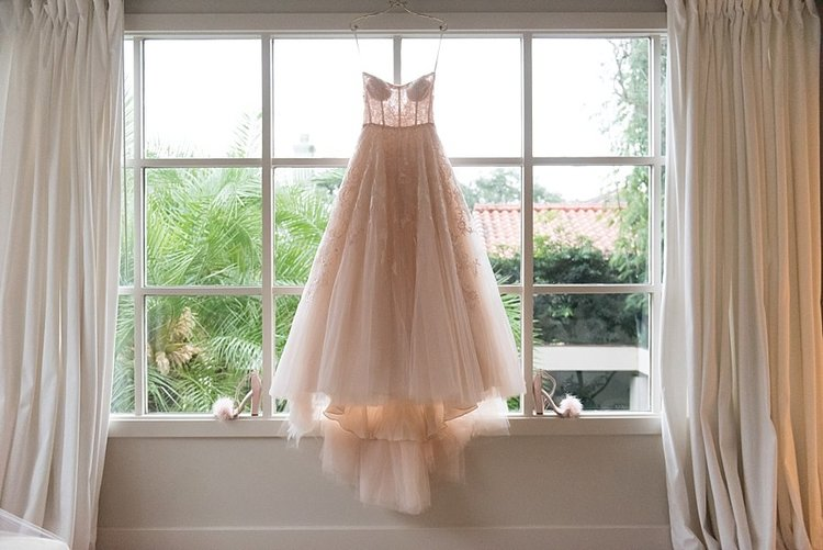 modern wedding gown hanging in front of a large window with greenery in the background and white drapes on the sides