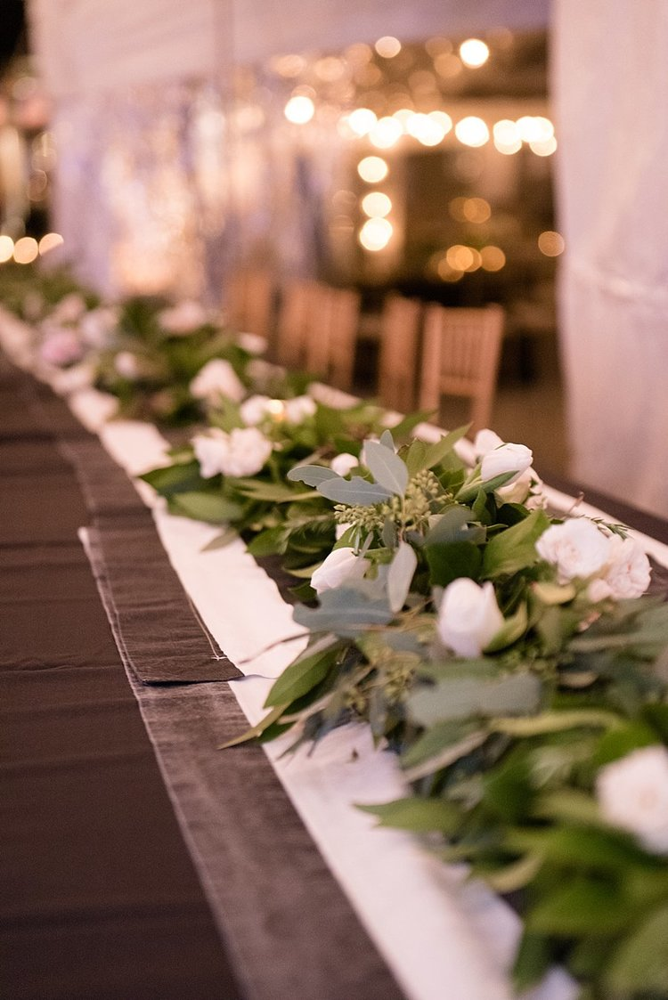 white roses and greenery runner on a dark table