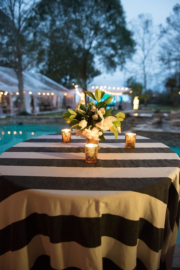 white flower centerpiece on a black and white tablecloth with a white tent in the background