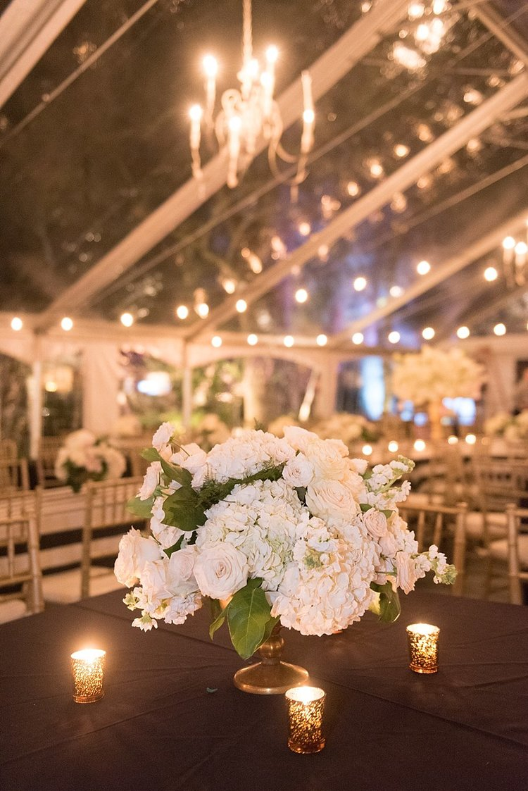 flower arrangement with roses and hydrangeas in a clear tent with a chandelier