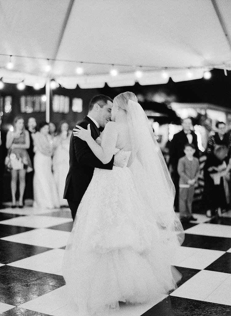 bride and groom dancing in a white tent on a black and white checkered dance floor