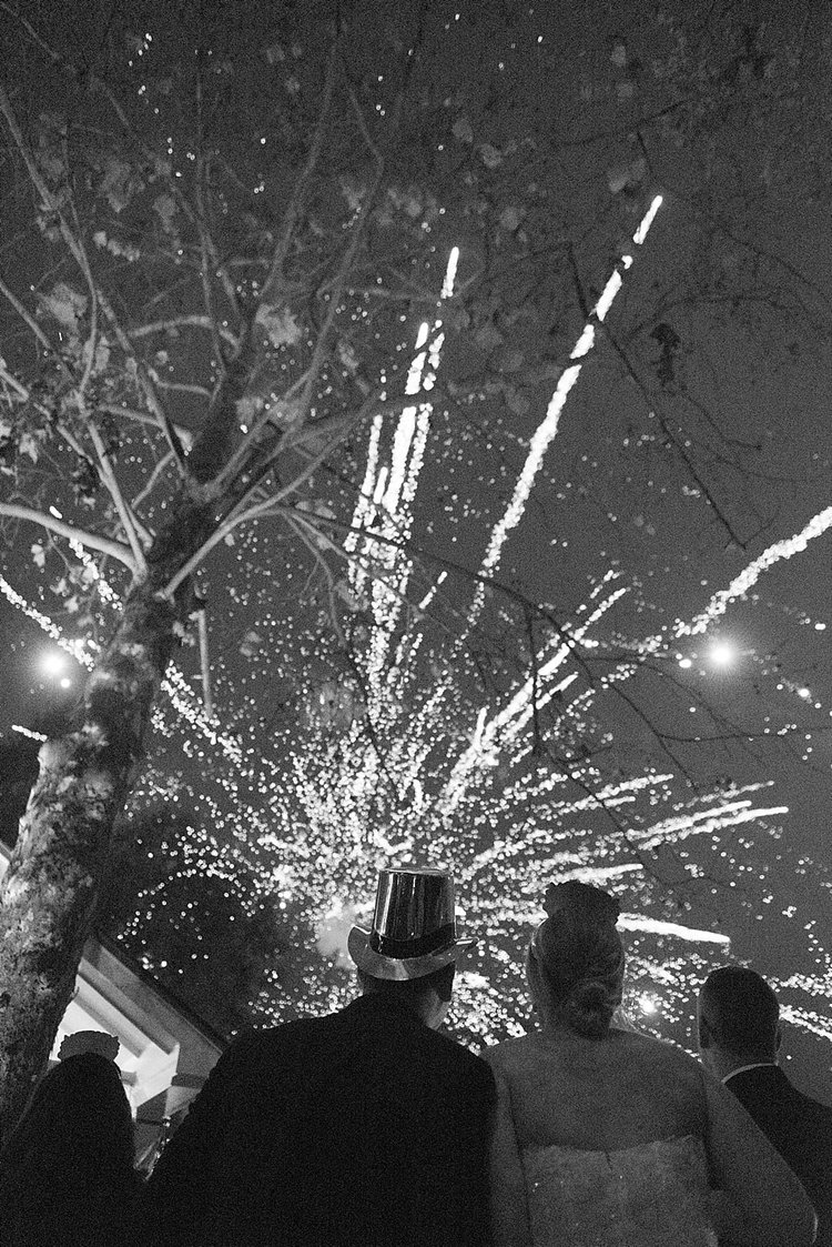 couple looking up a fireworks with New Years Eve hats on