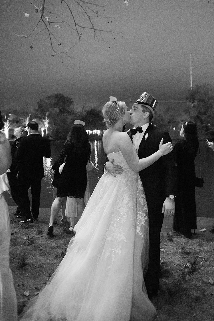 bride and groom dancing in front of a lake wearing wedding gown and tuxedo