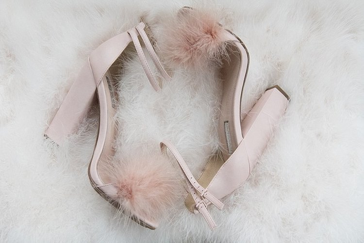 blush pink heels with a fun pink pom pom on the front laying on a white shaggy poof