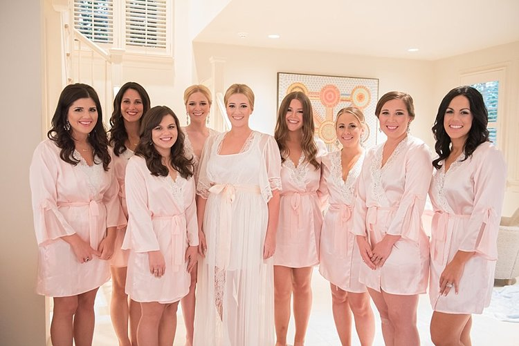 Bride and bridesmaids standing in their pink and white robes with hair and makeup done in a well lit room