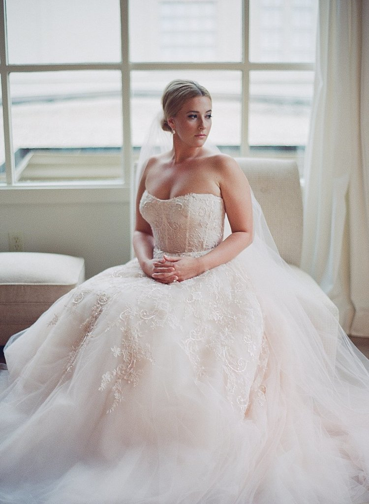 bride siting in a stunning detailed white strapless gown with a long white veil and a simple bun updo