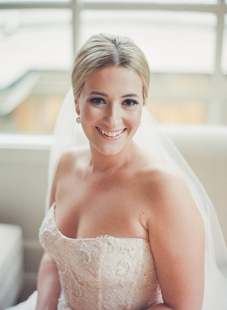 Beautiful bride smiling for a photo with her white veil draping over her shoulders