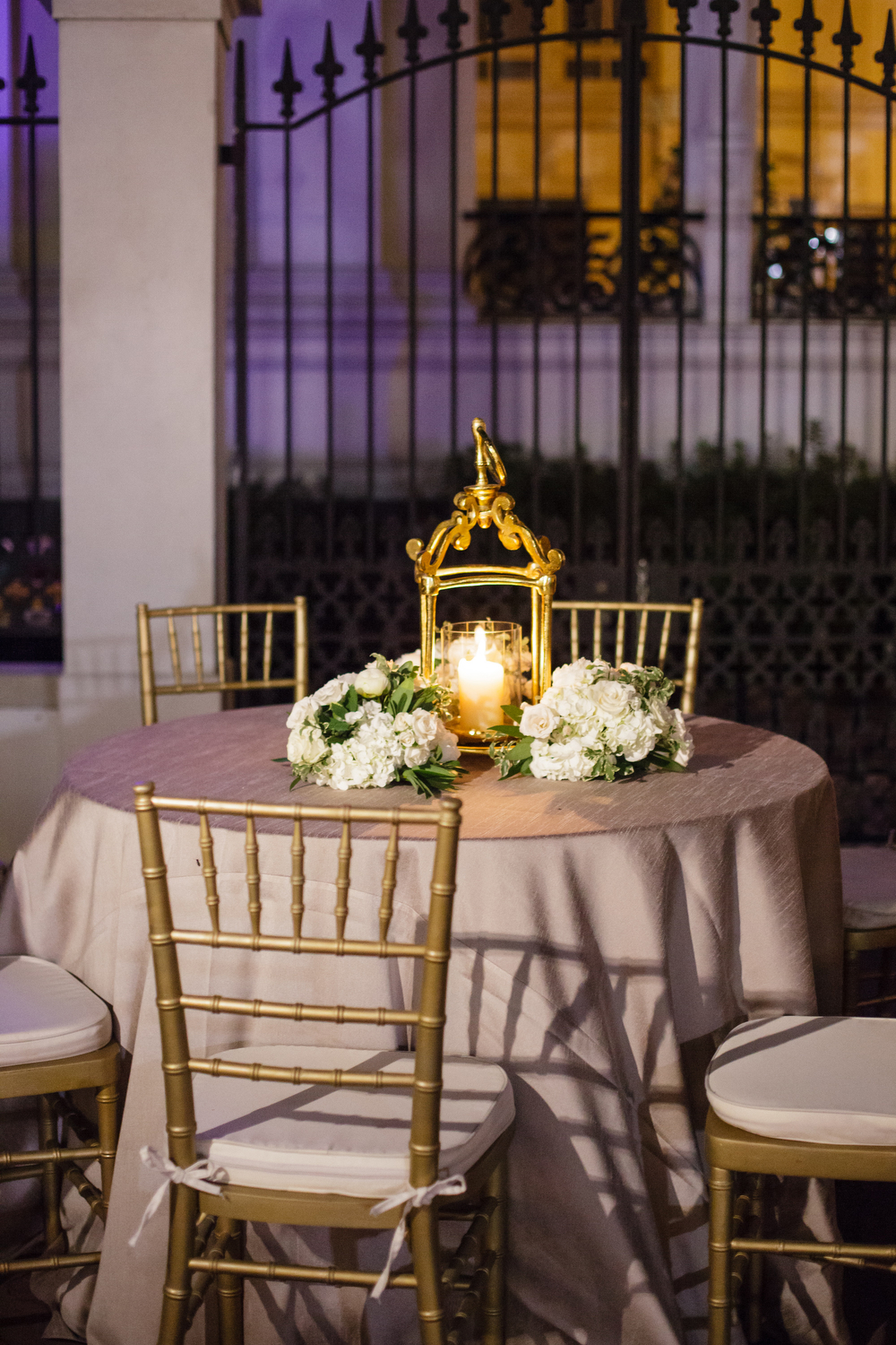 white hydrangea flowers on a table with golden lanterns in an outdoor courtyard wedding reception at night