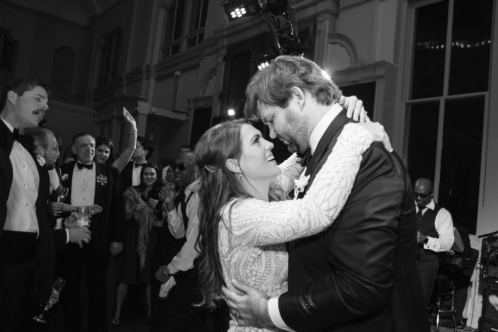 bride and groom first dance while looking into each others eyes on the dance floor