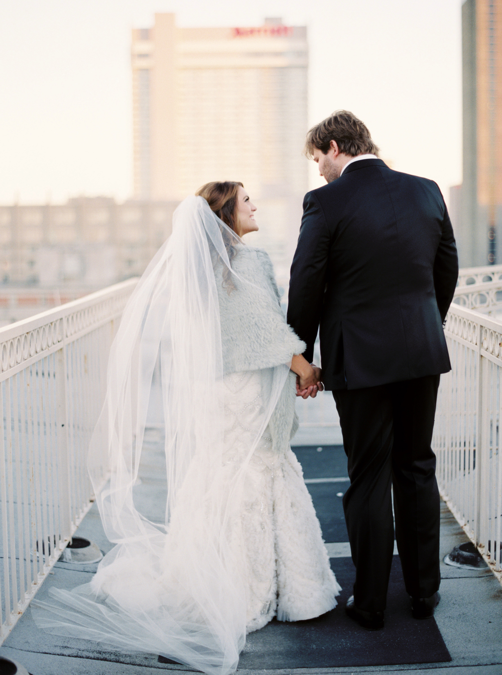 bride and groom walking away from the camera hand in hand with city skyline backdrop