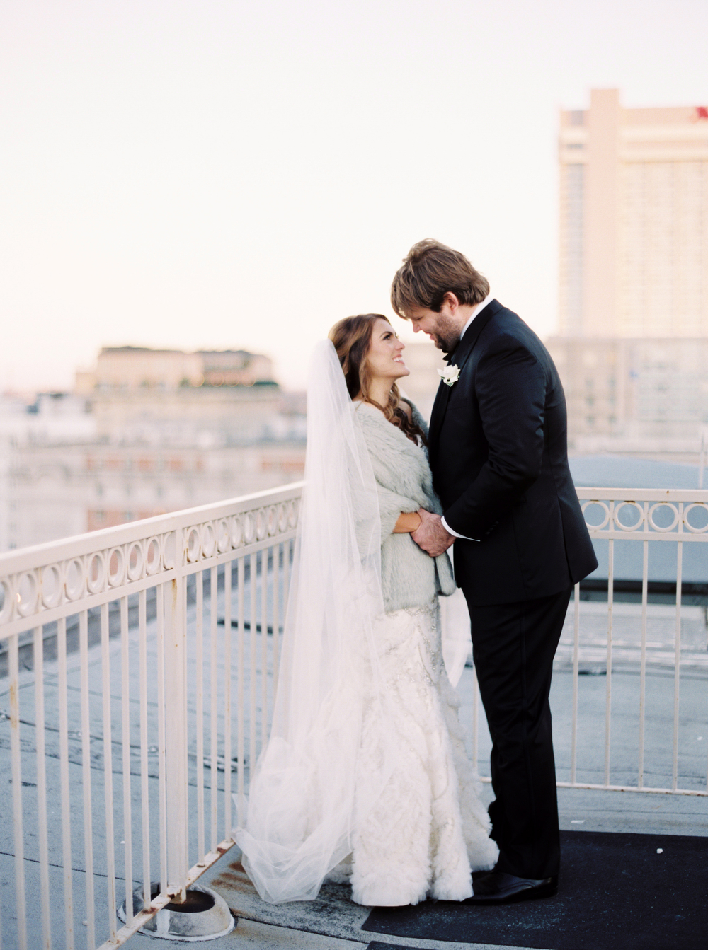 bride and groom holding each other and looking into their eyes with city in background