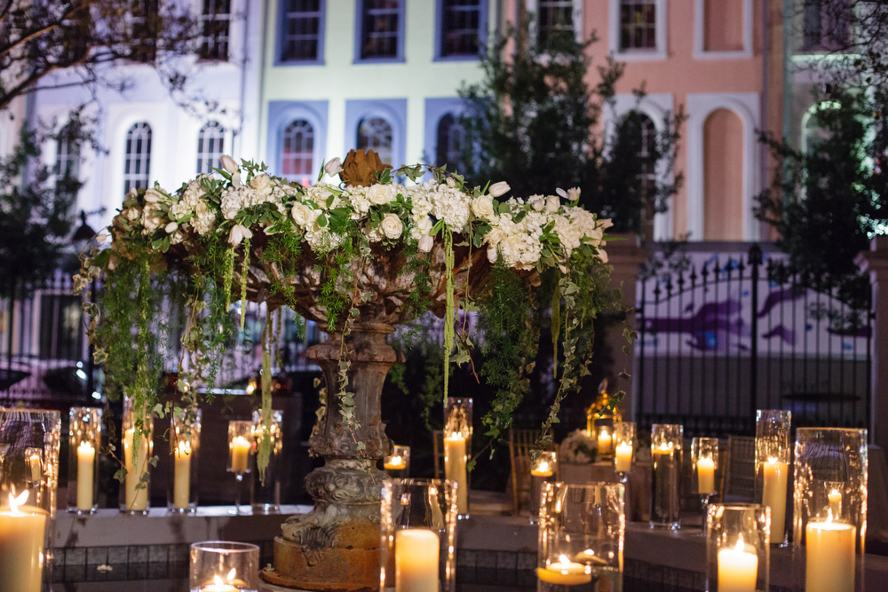 fountain with white and green floral decor and candle light surrounding in a courtyard at night