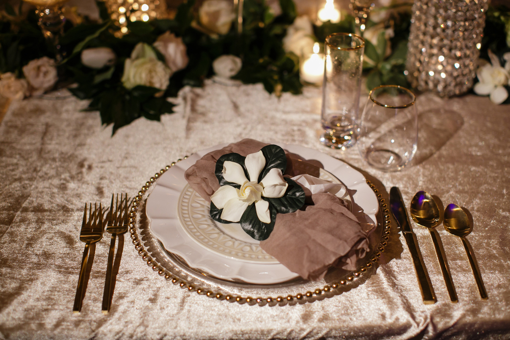 wedding reception place setting with velvet linen, beaded gold charger, white place setting, gray napkin and single garden blossom