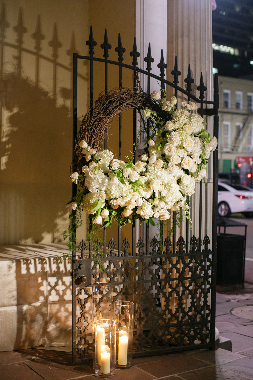 asymmetrical floral wreath on open gate at night with candle light at reception venue