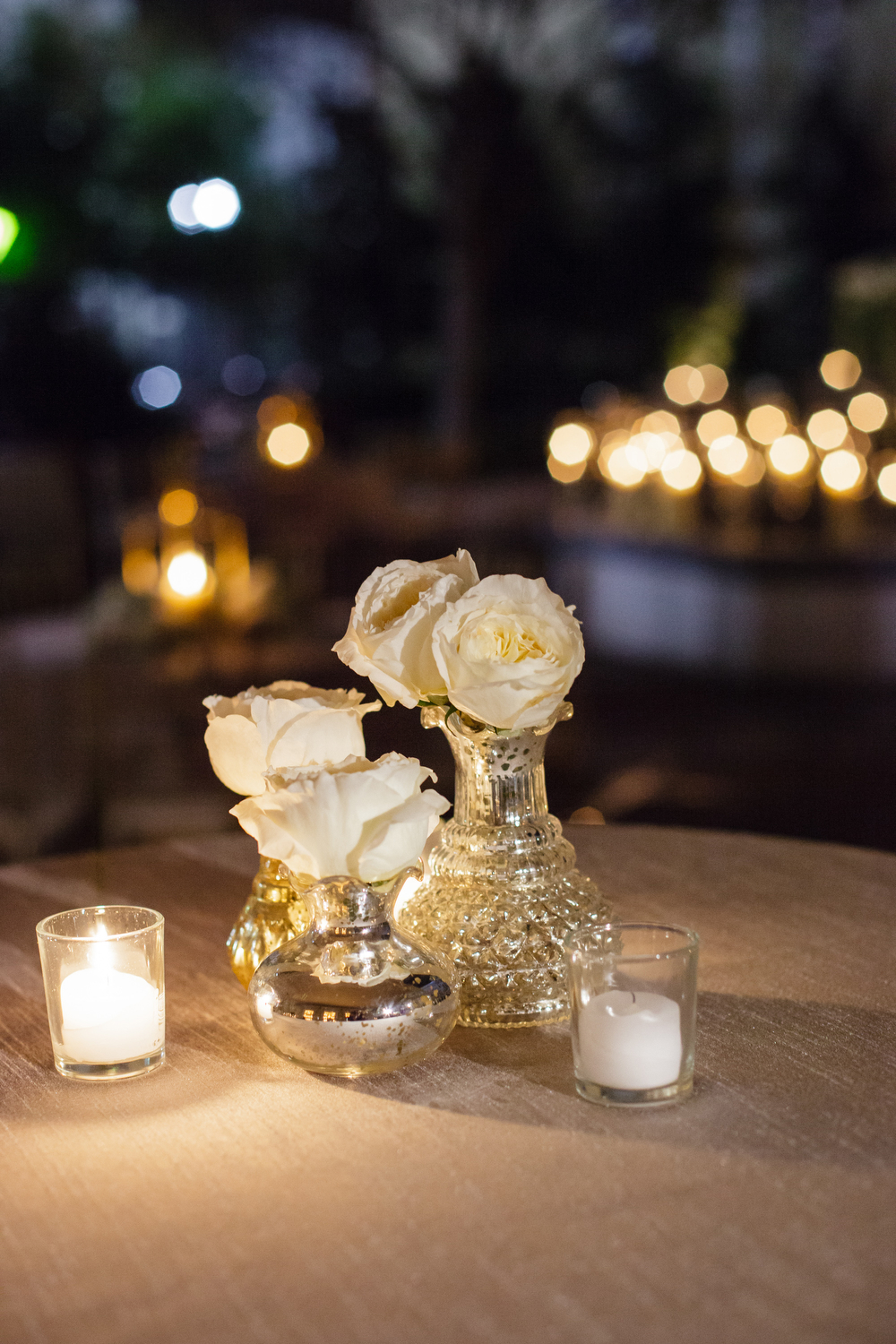 white florals in antique gold bud cases on table top outdoors in a courtyard at night