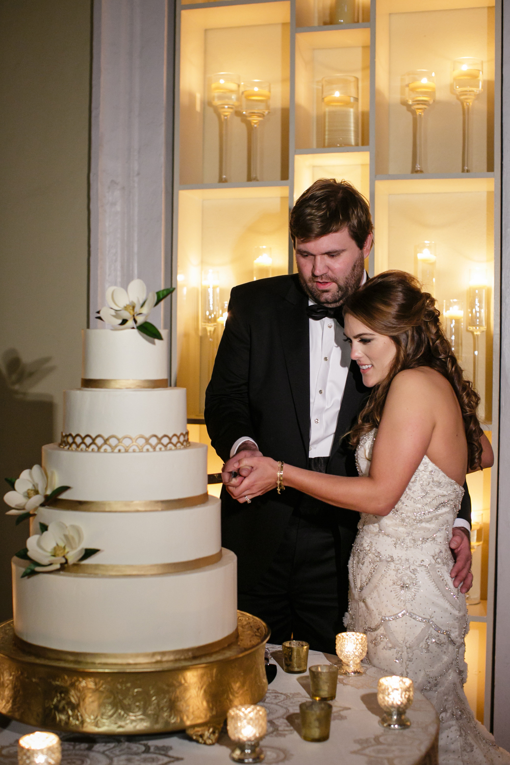 bride and groom cutting a large white and gold detailed wedding cake in front of a wall of candle light