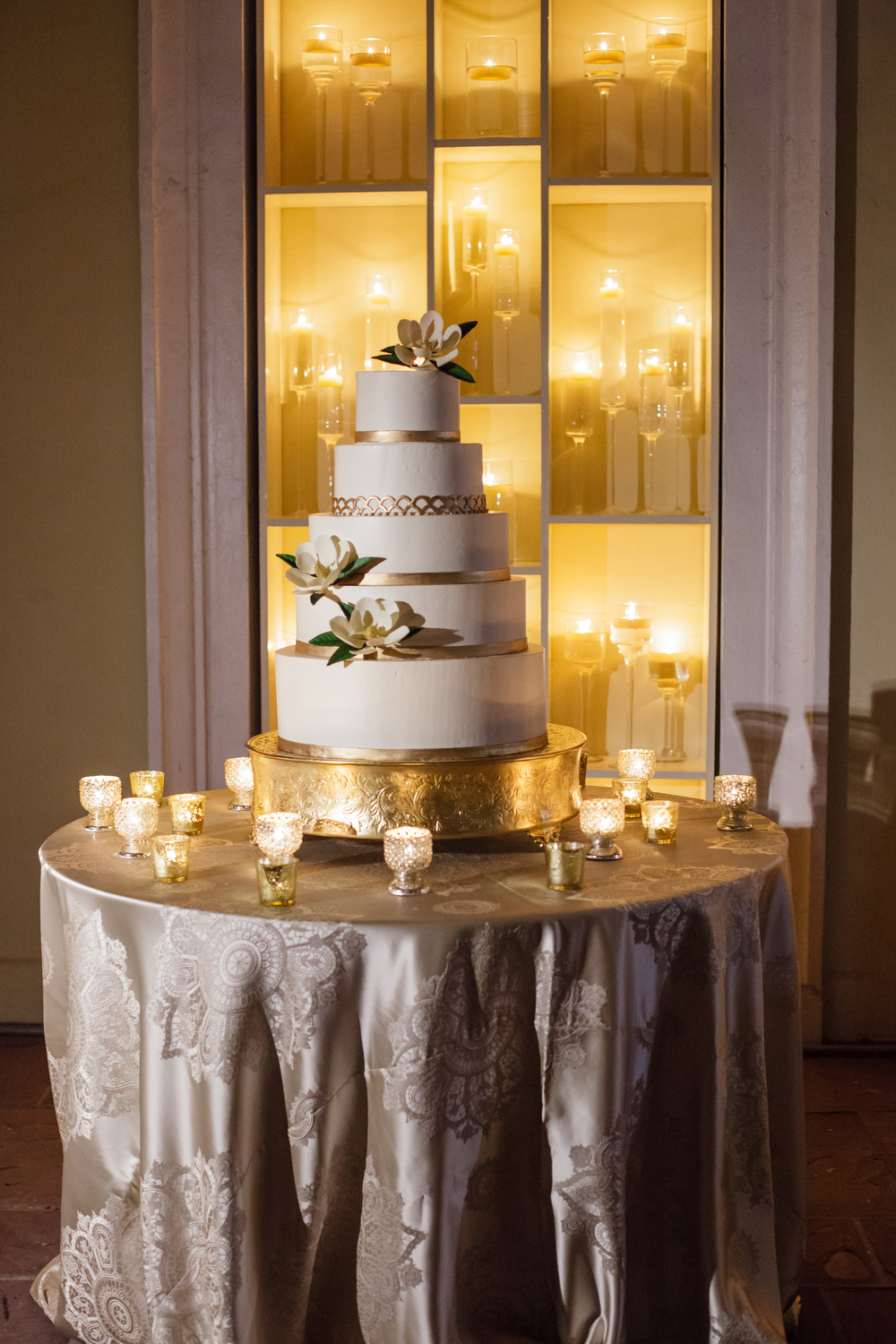 white and gold wedding cake in front of wall of candle light with magnolia flower details