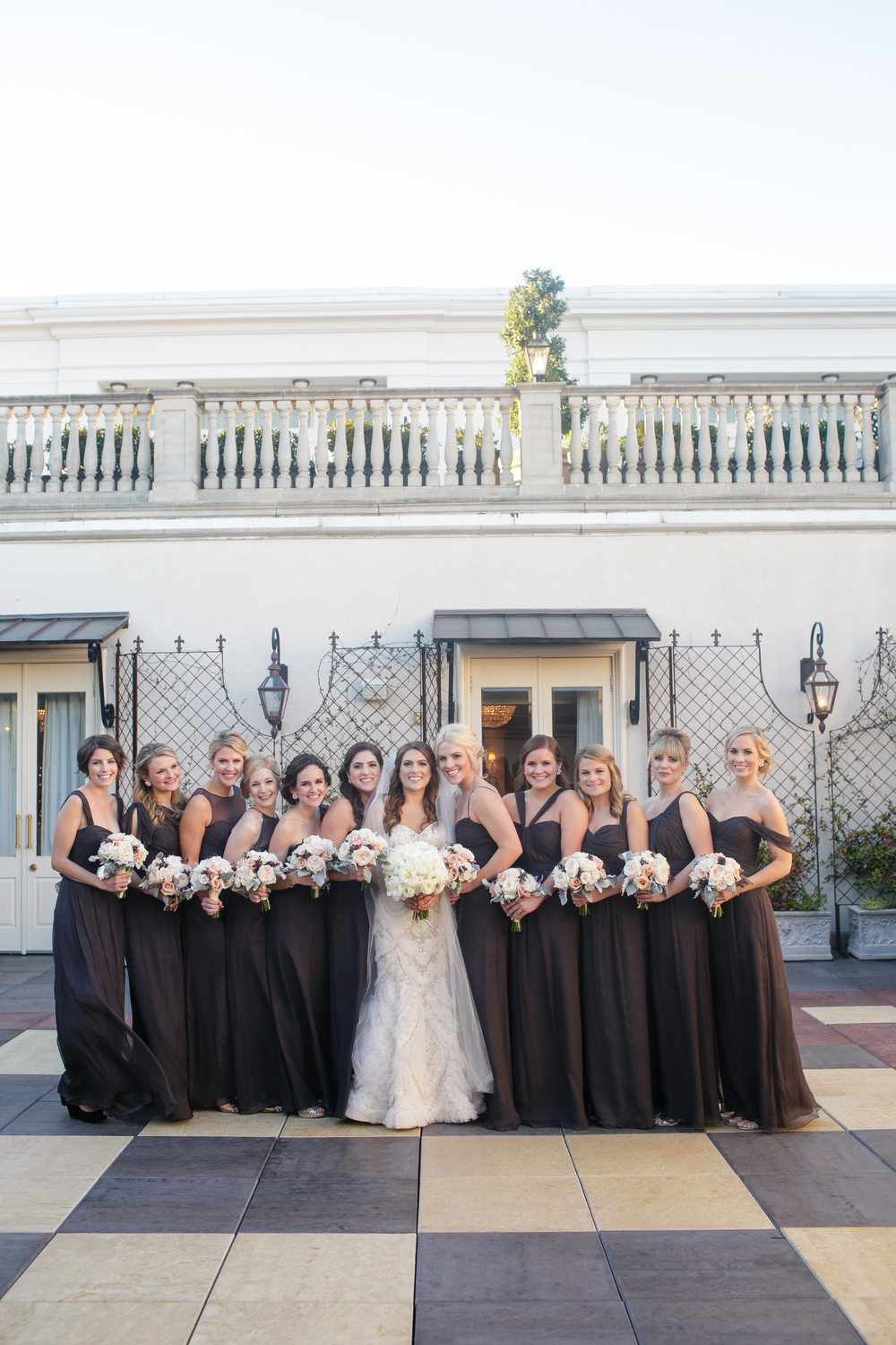 bride with bridesmaids in gray wedding dresses outside in a courtyard standing next to each other