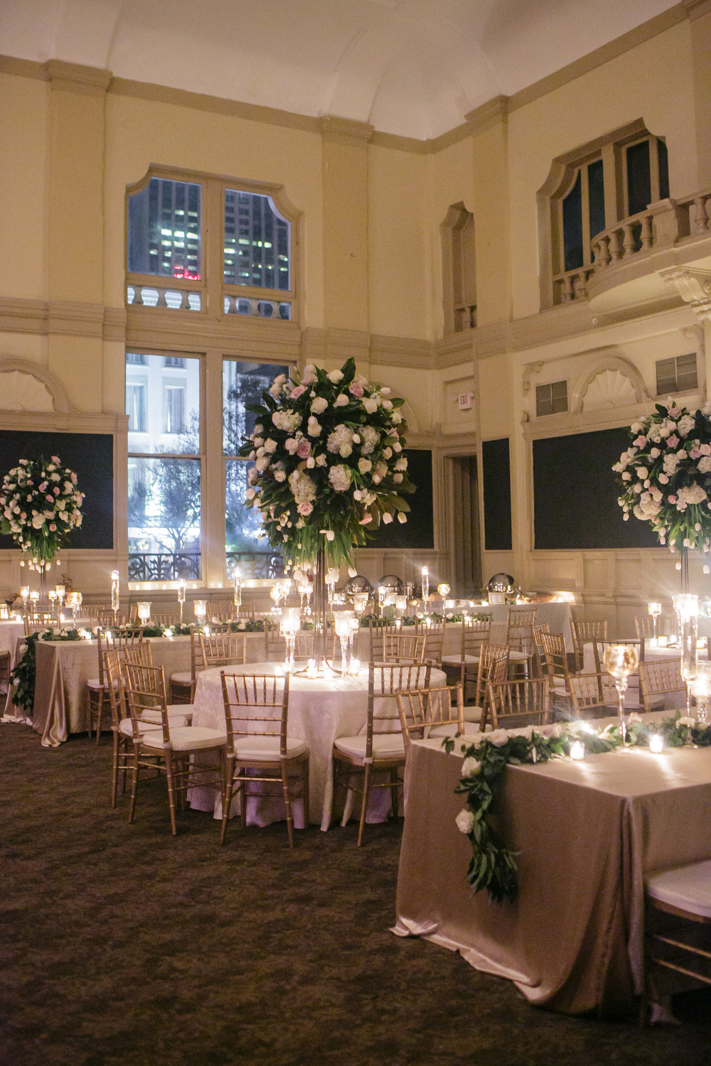 wide angle reception tables with lots of candle light and tall floral arrangements and low garland runners