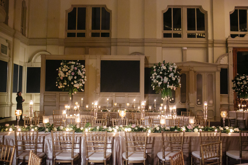 wide angel of room with long dinner tables and gold chiavari chairs with tall green and white floral arrangements