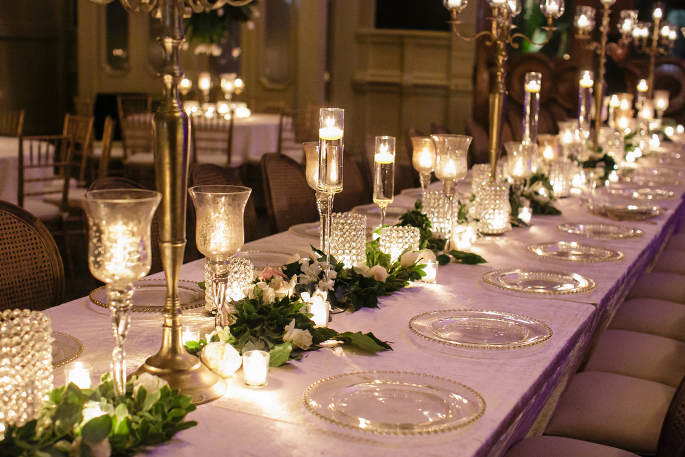 Long rows of various height candles and vases with green and white floral runner at a wedding reception
