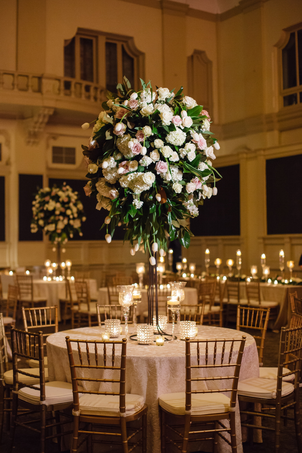 closeup of tall white and green wedding centerpiece arrangements on round tables with gold chairs in a wedding reception