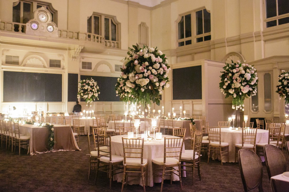 wide shot of reception room with round tables and long tables featuring candle light and tall white and green floral arrangements