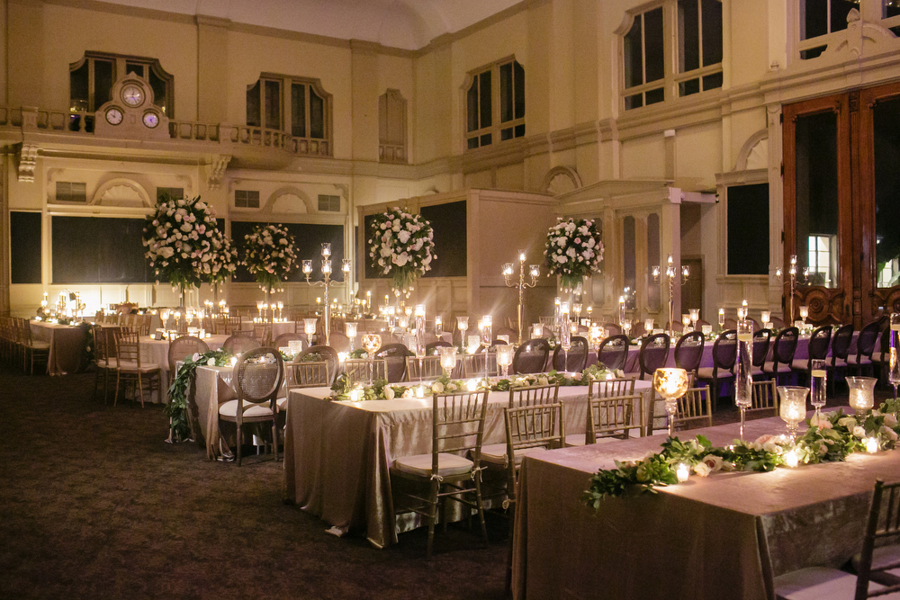 wide shot of large ballroom with long dinner tables featuring candle light and tall white and green floral arrangements