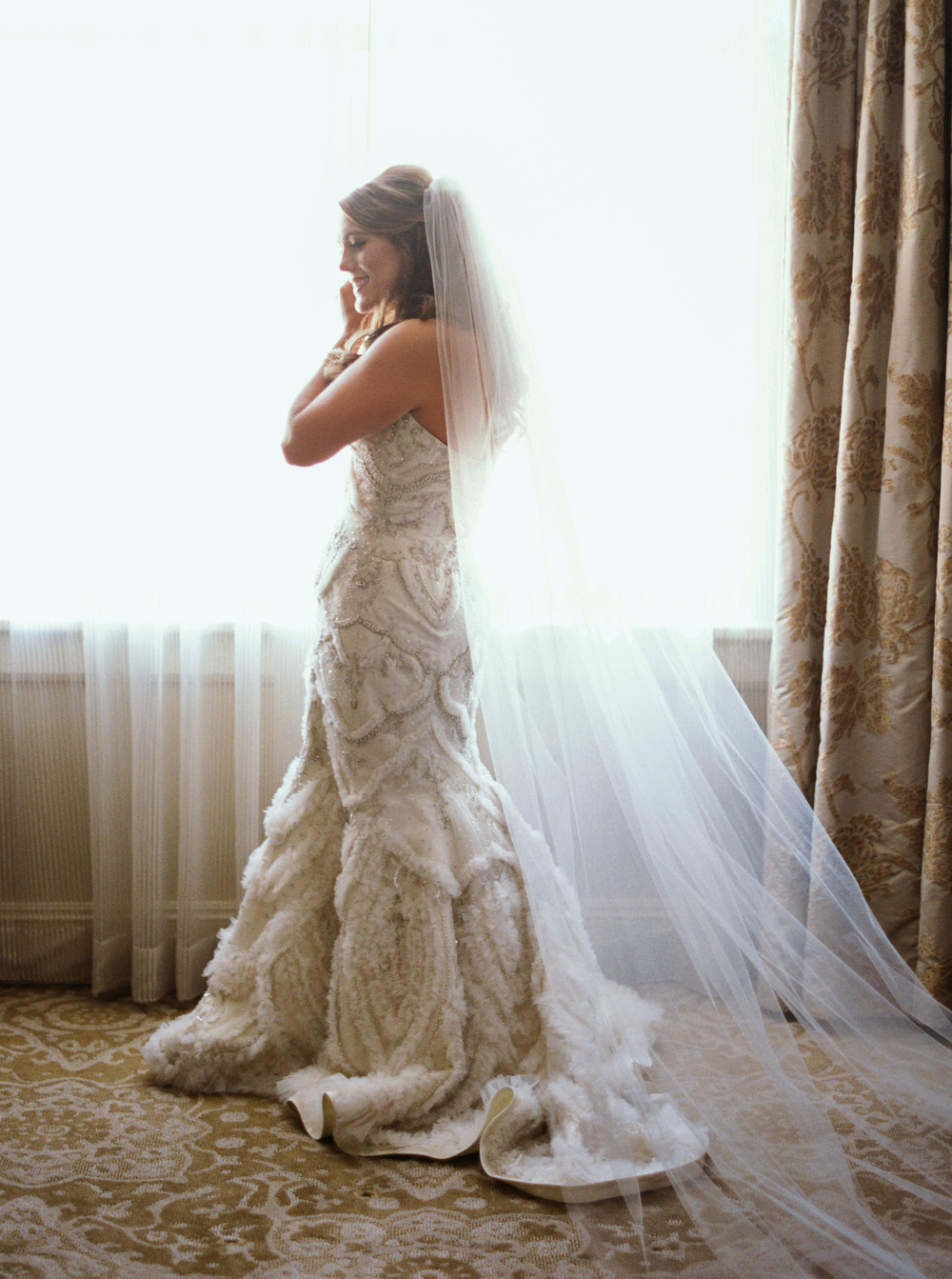 full length of bride standing in wedding gown with long veil by a window