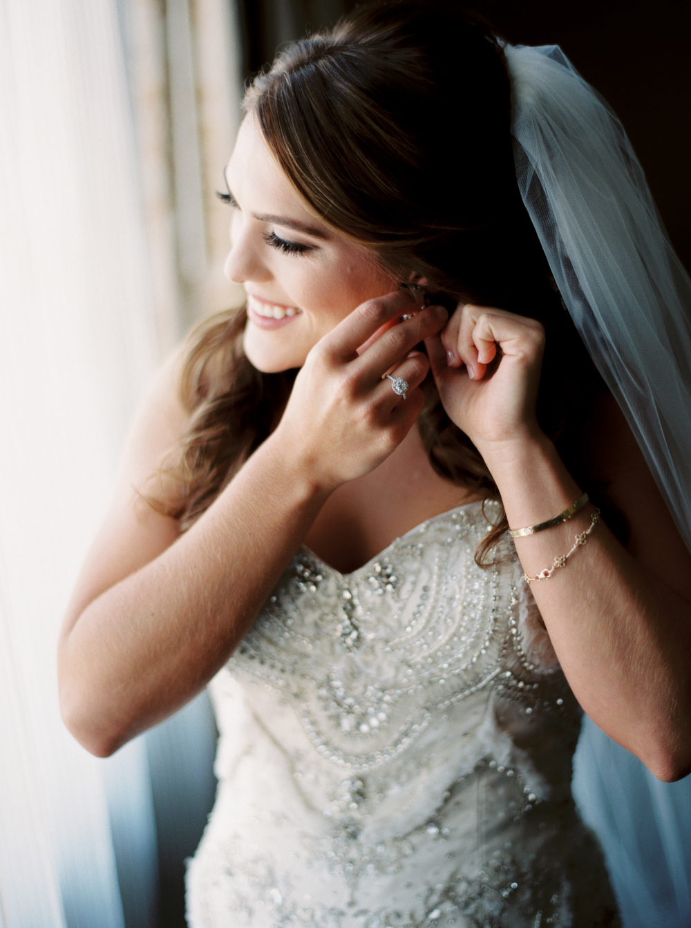 bride smiling as she puts on her earrings standing in the light of a window with veil trailing down