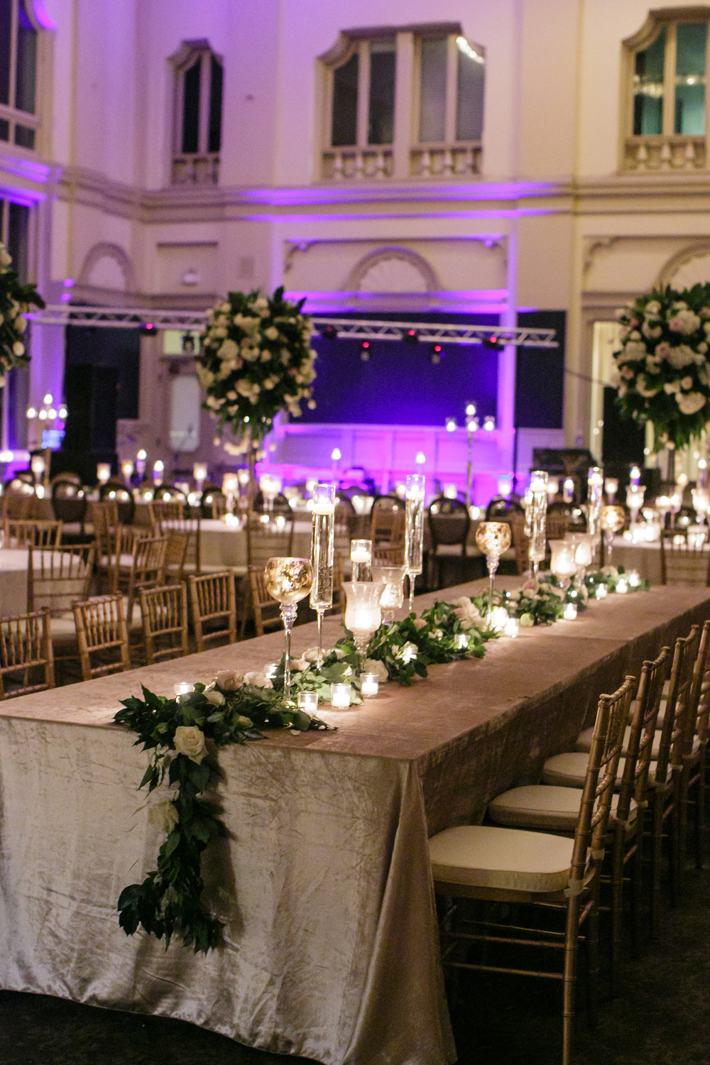 seated wedding reception tables with long greenery and white floral runners with candles and architectural details