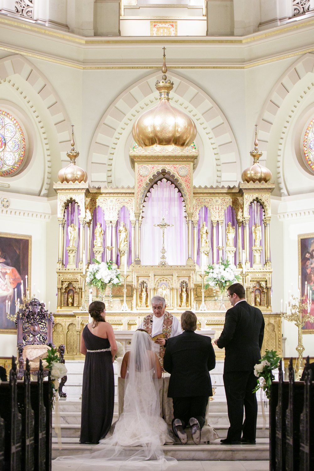 bride and groom kneeling at wedding chapel altar during catholic ceremony