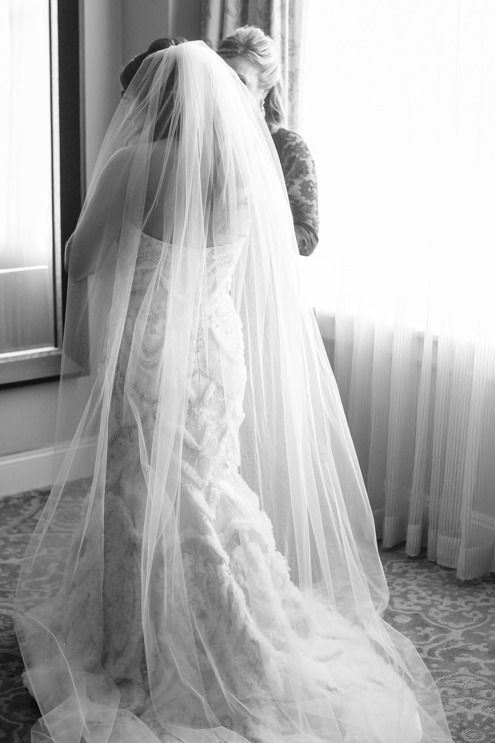 back of bride getting dressed with long cathedral length veil in a window
