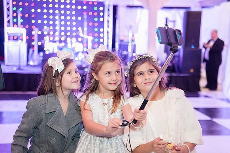 litttle girls on black and white dancefloor taking a selfie with a selfie stick and wearing white bow headbands