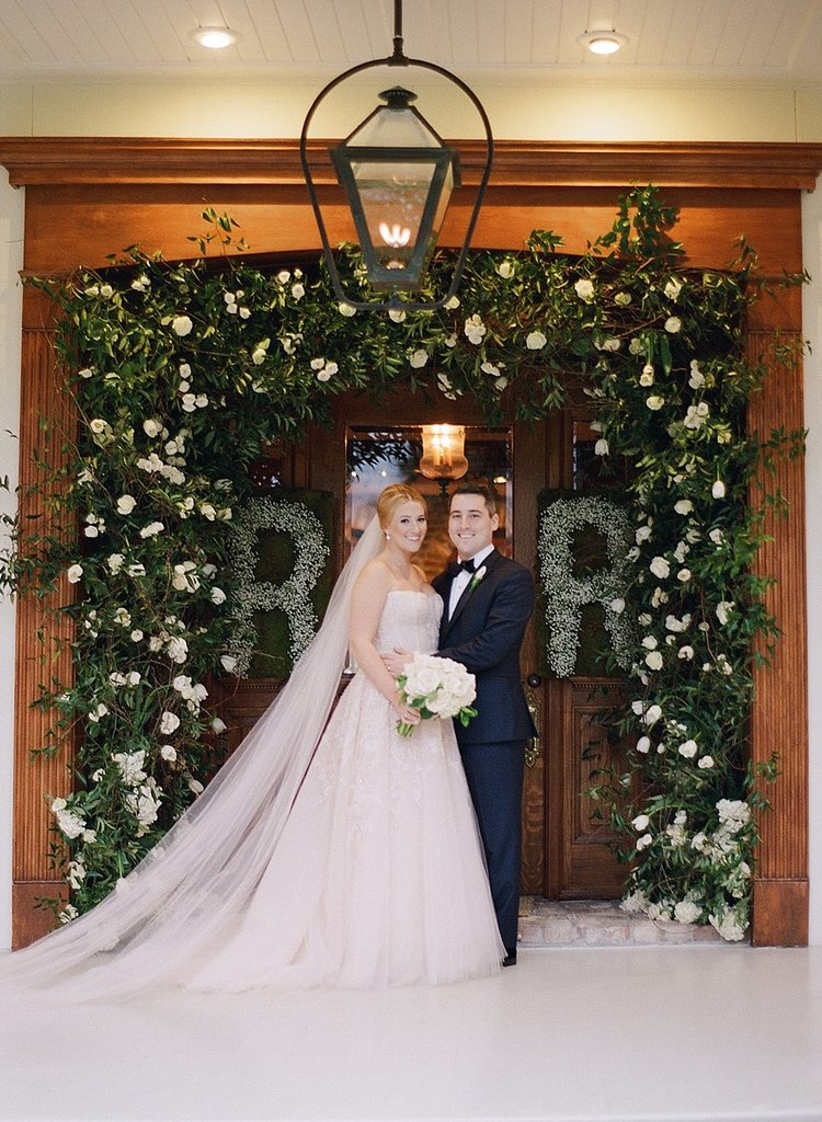 bride and groom standing in front of doorway with a magnificent green and white arch and initials our of flowers