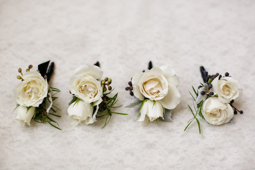 four white rose and rosemary boutonnieres lined up on a lace backdrop