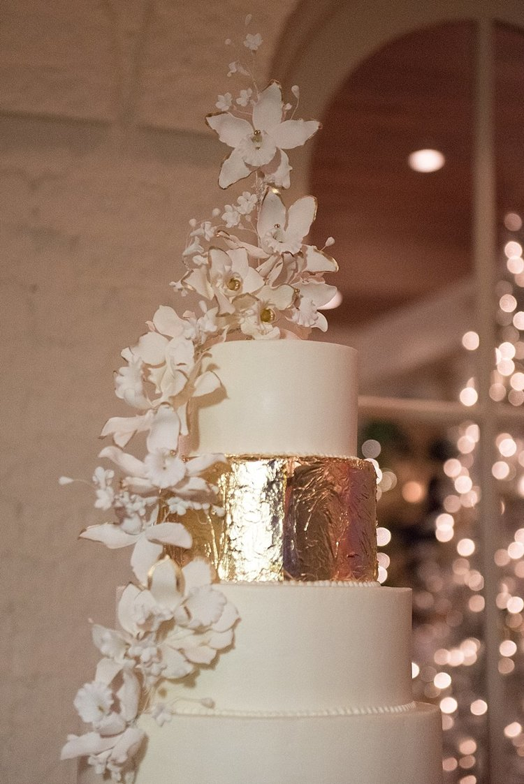 white and gold four tier wedding cake with delicate flowers down the side