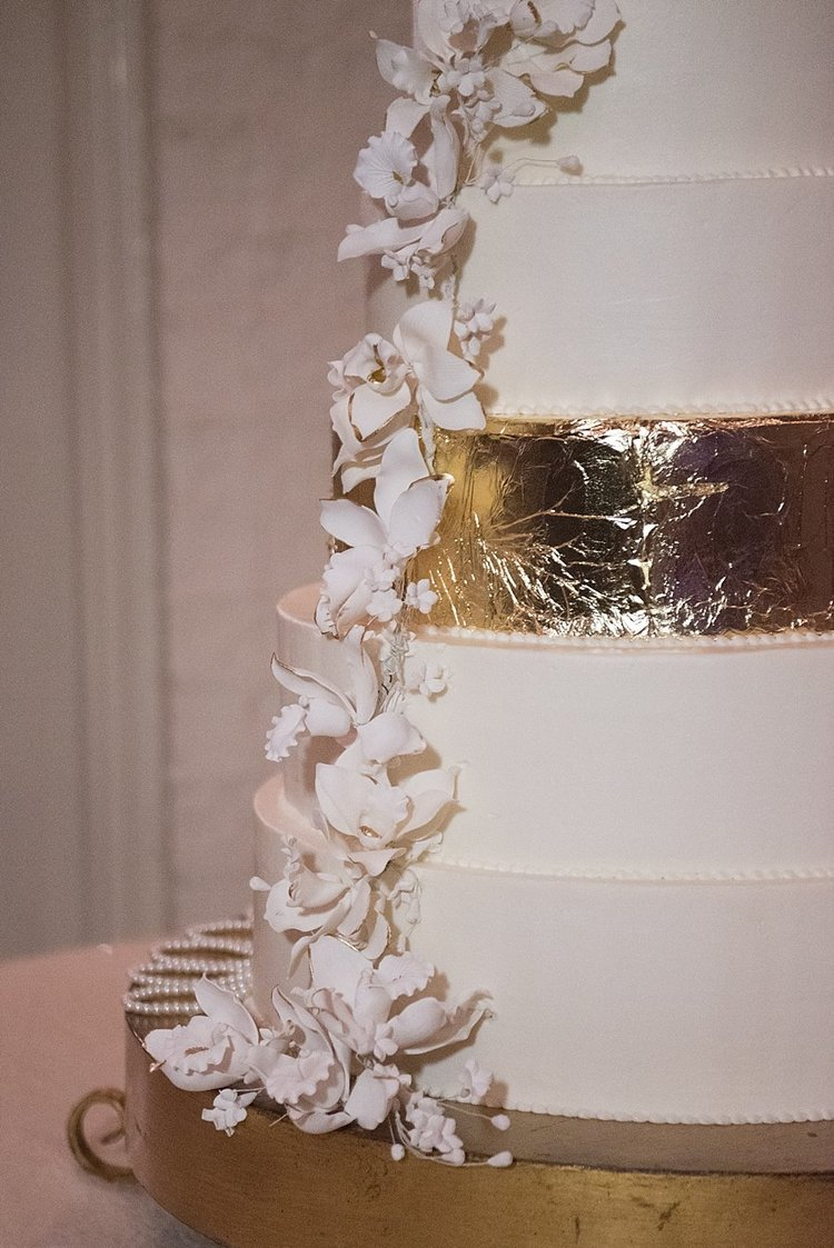gold and white wedding cake with intricate white edible flowers down the side