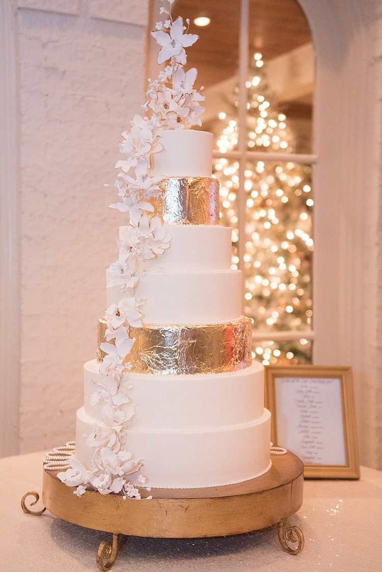 7 tier white and gold wedding cake with delicate sugar flowers traveling down the cake