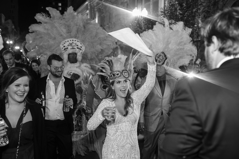 bride waving white napkin in the air during a second line parade with her groom and wedding guests